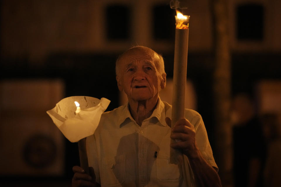 A man holds a torch during a procession joined by tens of thousands in Budapest, Hungary, Saturday, Sept. 11, 2021, the day before the final mass of International Eucharistic Congress on which will be attended by Pope Francis. Pope Francis is making his first foreign trip since undergoing intestinal surgery in July, a four-day visit to Hungary and Slovakia starting Sunday. (AP Photo/Vadim Ghirda)