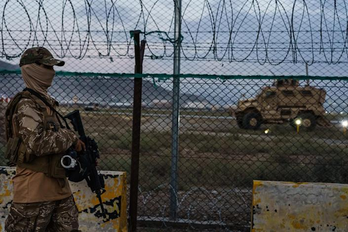 A Taliban fighter walks with a rifle outside a fence