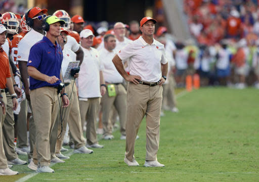 FILE - In this Saturday, Sept. 7, 2019 file photo, Clemson head coach Dabo Swinney, center, and defensive coach Brent Venables, left, watch the action during the second half of an NCAA college football game against Texas A&M in Clemson, S.C. Tyler Davis didnt plan on starting this soon for Clemson, given the depth the Tigers had stockpiled at defensive tackle the past few seasons. Clemson coach Dabo Swinney and defensive coordinator Brent Venables had planned for the talent drain and had brought along several linemen like Williams and junior Xavier Kelly to take over. They didnt count on Davis forcing his way into the starting lineup. (AP Photo/Richard Shiro, File)