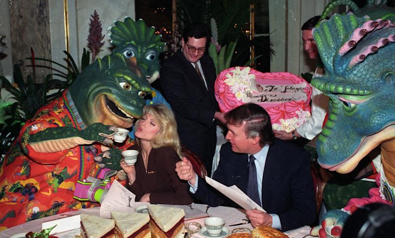 "Donald Trump watches as Marla Maples gets a kiss from Earl Sinclair of TV's ""Dinosaurs"" during lunch at the Trump Plaza Hotel on Nov. 2, 1992."