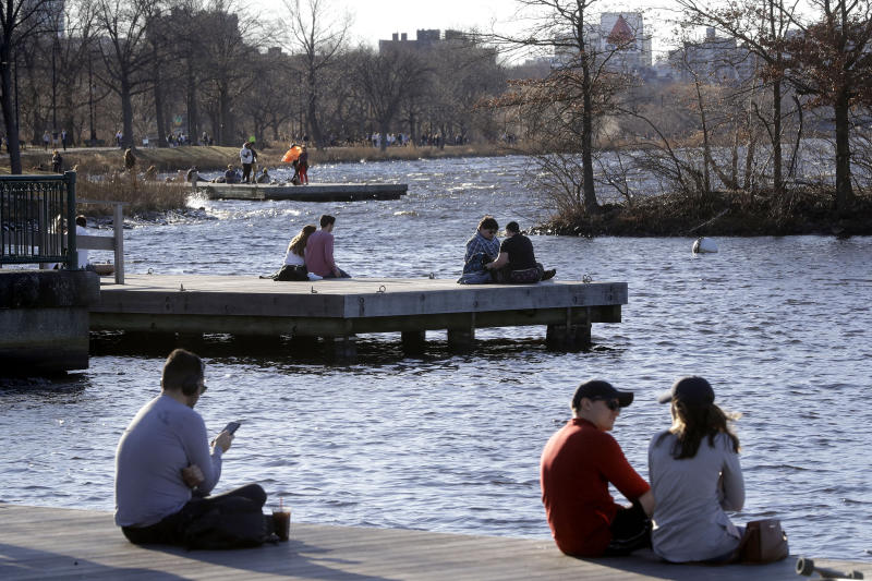 People sit on docks in the Charles River Esplanade park, in Boston, Sunday, Jan. 12, 2020, while enjoying unseasonably warm weather. Temperatures climbed into the low 70s in many places in the state Sunday. (AP Photo/Steven Senne)
