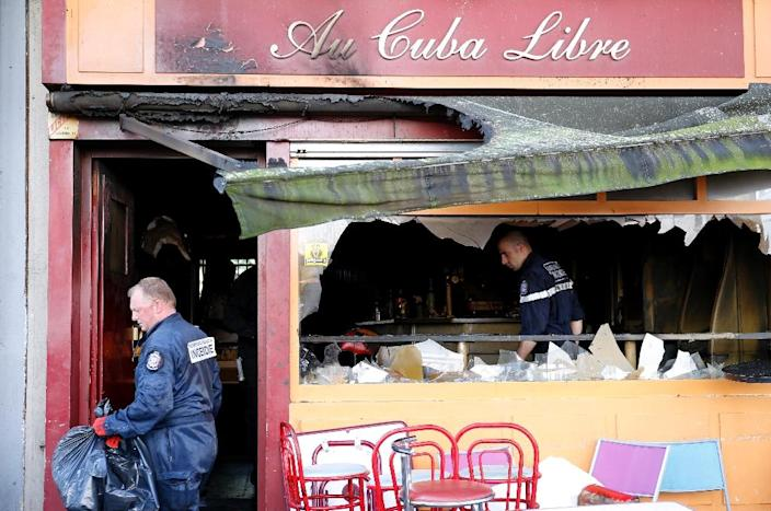 Police officers and fire investigators inspect the damaged Au Cuba Libre bar in Rouen, northern France, on August 6, 2016, after a fire broke out overnight in the bar during a birthday party (AFP Photo/Matthieu Alexandre)