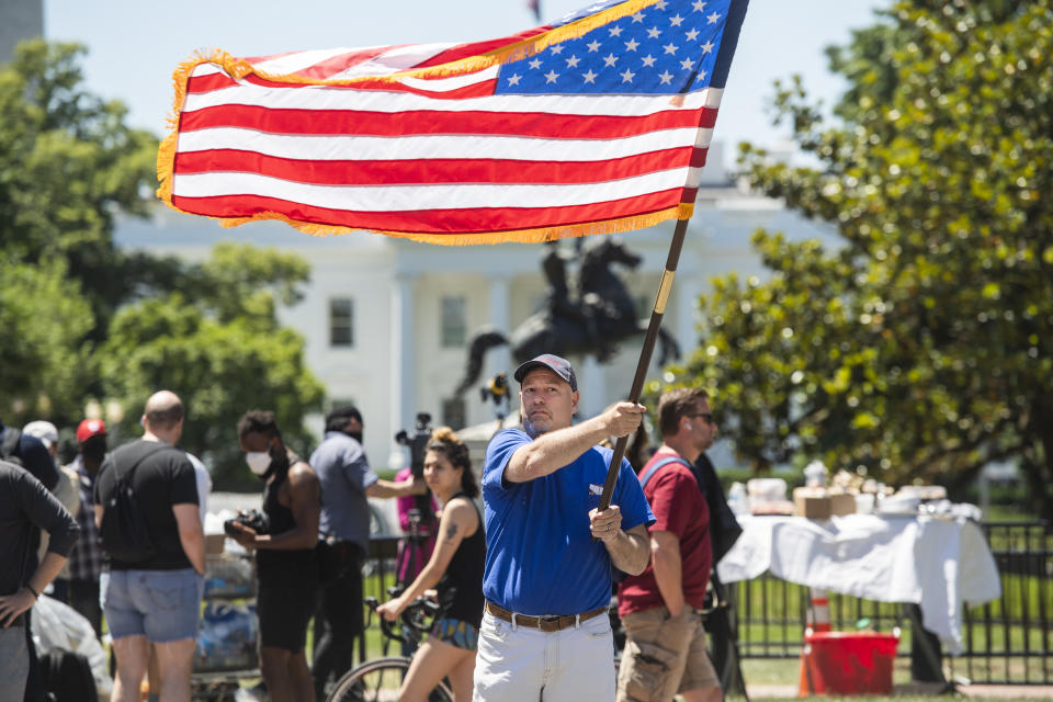 Un hombre hondea una bandera de Estados Unidos delante de la Casa Blanca. (Foto: Tom Williams/CQ-Roll Call, Inc via Getty Images)