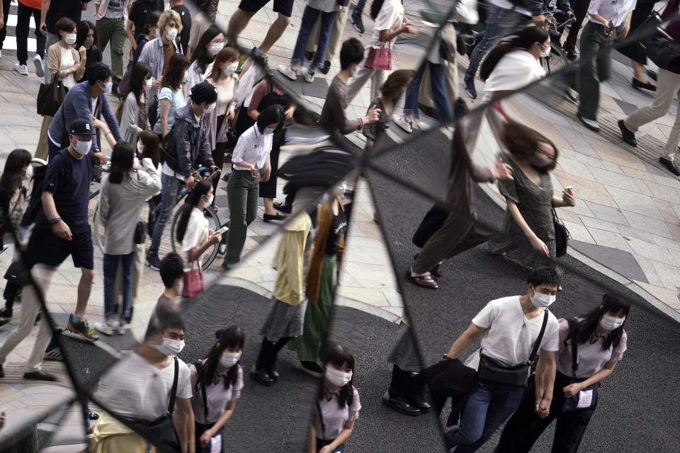 People wearing protective masks to help curb the spread of the coronavirus are reflected on mirror wall of a shopping building Monday, Sept. 21, 2020, in Tokyo. The Japanese capital confirmed more than 90 coronavirus cases on Monday marking Respect-for-the-Aged Day holiday. (AP Photo/Eugene Hoshiko)