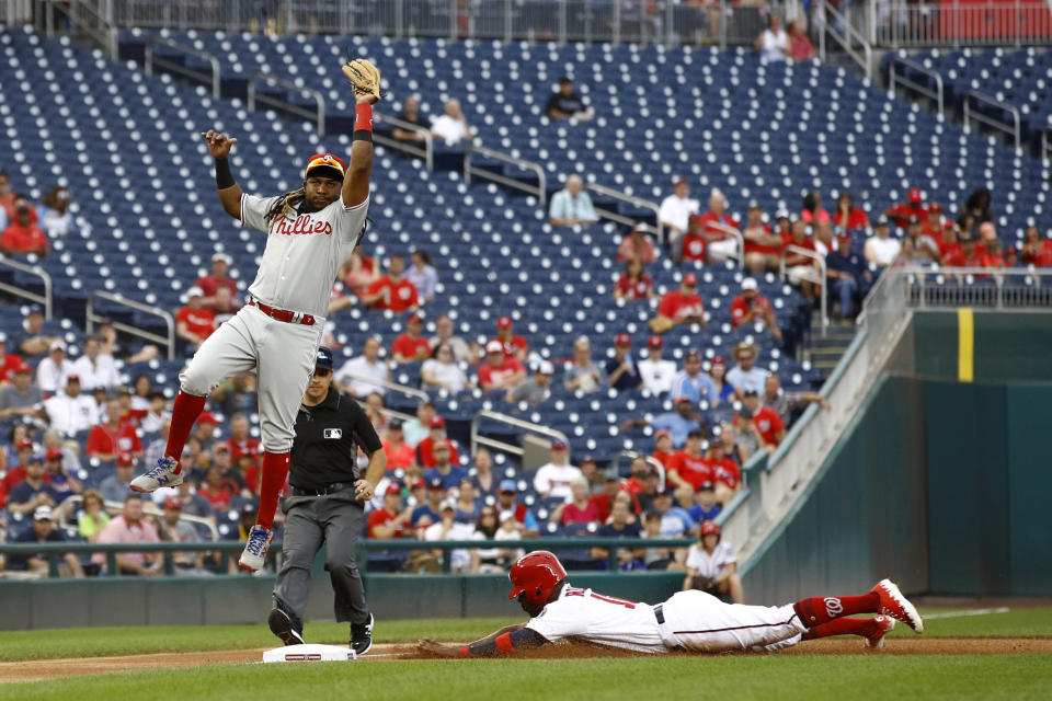 Washington Nationals' Victor Robles, bottom right, safely steals third base in front of Philadelphia Phillies third baseman Maikel Franco in the first inning of a baseball game, Thursday, Sept. 26, 2019, in Washington. (AP Photo/Patrick Semansky)
