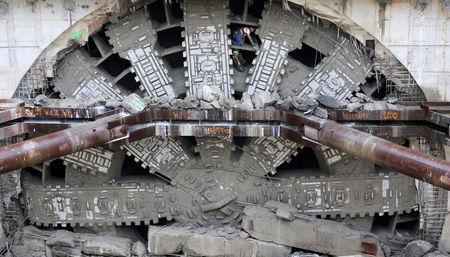 Workers celebrate by posing inside the giant teeth of Seattle's tunnel-drilling machine, Bertha, the world's largest tunnel-boring machine at its completion into the disassembly pit in Seattle, Washington, U.S., April 4, 2017. REUTERS/Karen Ducey