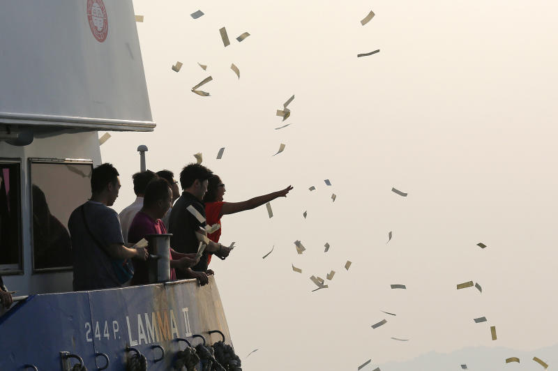 Relatives of the victims throw paper money Tuesday, Oct. 2, 2012 as they pay tribute to the ill-fated people aboard a boat that sank Monday night near Lamma Island, off the southwestern coast of Hong Kong Island. The boat packed with revelers on a long holiday weekend collided with a ferry and sank off Hong Kong, killing at least 36 people and injuring dozens, authorities said. (AP Photo/Vincent Yu)