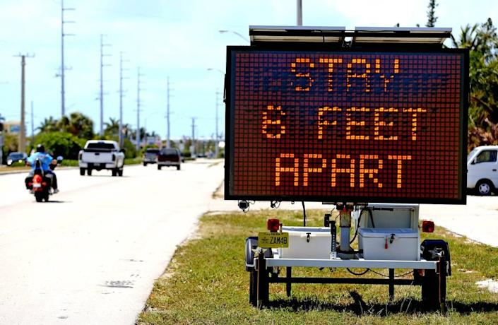 Signs along U.S. 1 in Marathon in the Florida Keys ask drivers to practice social distancing as the Keys prepare to shut down on Sunday closing hotels and restaurants because of coronavirus fears, March 21, 2020.