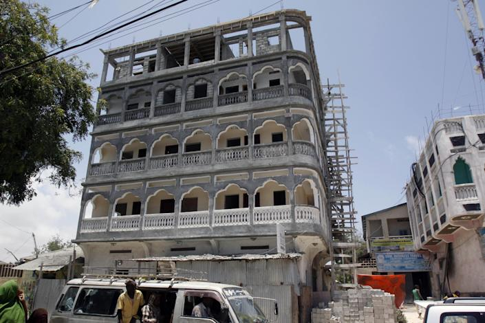 In this Thursday, Sept. 19, 2013 photo, a Somali woman looks at a four storey building under construction in the Somali capital, Mogadishu. Despite the occasional militant attack, this seaside city's real estate market has seen an upsurge in demand over the last two years, thanks in part to security gains made following the ouster of the al-Qaida-linked Islamic rebels of al-Shabab. (AP Photo/Farah Abdi Warsameh)