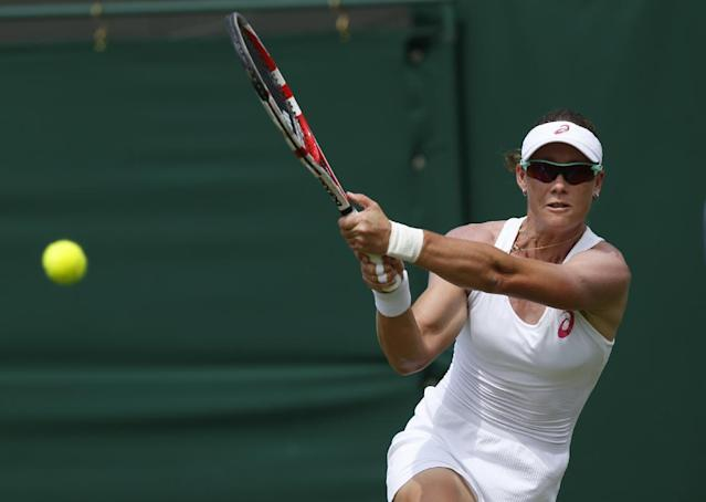 Australia's Samantha Stosur plays a return to Belgium's Yanina Wickmayer during their first round match at the All England Lawn Tennis Championships in Wimbledon, London, Monday, June 23, 2014. (AP Photo/Sang Tan)