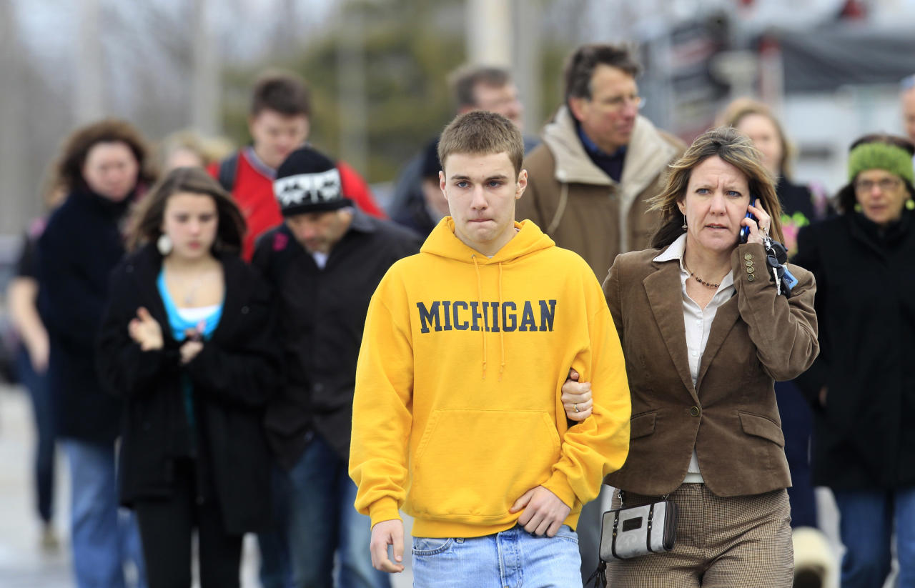 Students leave with parents from Maple Elementary School after a shooting at Chardon High School Monday, Feb. 27, 2012, in Chardon, Ohio. Students assembled at Maple Elementary School after a shooting took place at the high school. A gunman opened fire inside the high school's cafeteria at the start of the school day, wounding four students, officials said. A suspect is in custody. (AP Photo/Tony Dejak)