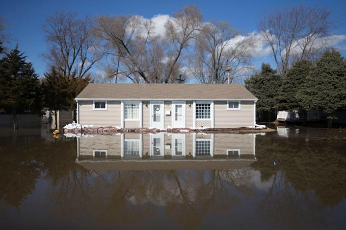 The Rock River crested its banks and floods a home on Old Harlem Road on Saturday, March 16, 2019, in Machesney Park, Ill.