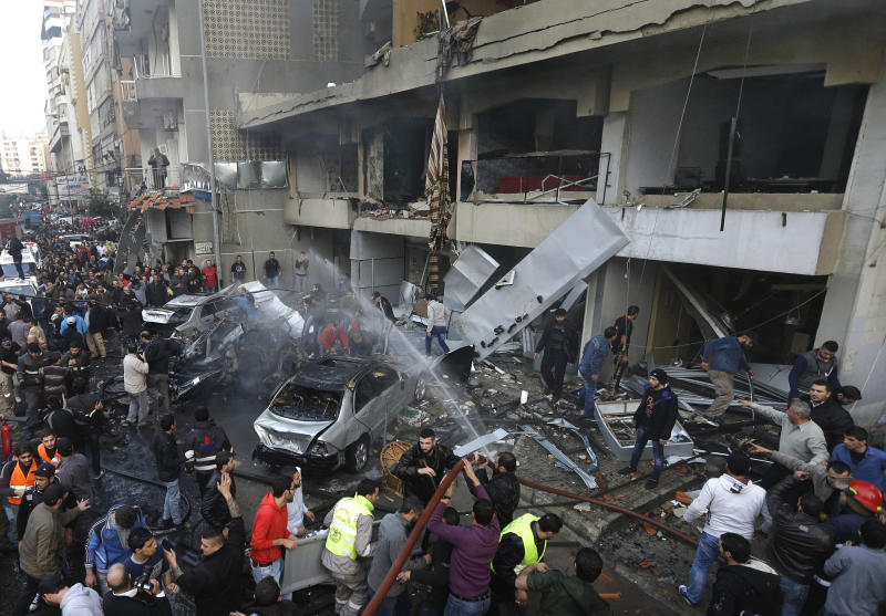 Lebanese citizens gather at the site of an explosion in a stronghold of the Shiite Hezbollah group at the southern suburb of Beirut, Lebanon, Thursday, Jan. 2, 2014. The explosion took place during rush hour in the Haret Hreik neighborhood, killing several people, setting cars ablaze and sending a column of black smoke above the Beirut skyline. (AP Photo/Hussein Malla)
