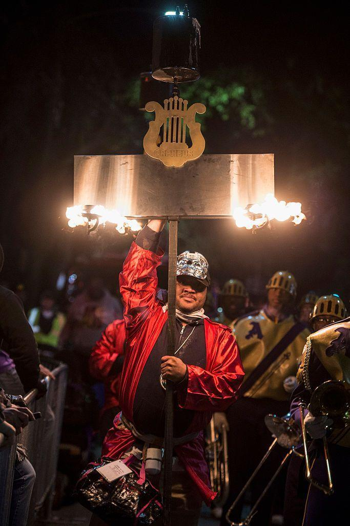 """<p>The story of how flambeaux walkers came to carry the torch is a lesson in Black New Orleans history. Flambeaux—a name derived from <em>flambe</em>, the French word for """"flame""""—have existed since that first Fat Tuesday parade in 1857. Originally, flambeaux <a href=""""https://thesocietypages.org/socimages/2015/02/16/the-flambeaux/"""" rel=""""nofollow noopener"""" target=""""_blank"""" data-ylk=""""slk:were carried by slaves and free Creole men of color"""" class=""""link rapid-noclick-resp"""">were carried by slaves and free Creole men of color</a>, twirling them with flair for tip money while lighting the parade path for onlookers and the well-heeled white members of the Krewe of Comus. Even in the era of street lamps <a href=""""https://www.youtube.com/watch?v=mRXg5Gq9iYY"""" rel=""""nofollow noopener"""" target=""""_blank"""" data-ylk=""""slk:you'll still spot flambeaux"""" class=""""link rapid-noclick-resp"""">you'll still spot flambeaux</a> in several parades each year. </p>"""