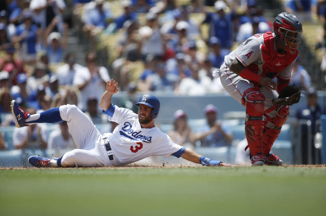 Los Angeles Dodgers Chris Taylor, left, scores past Los Angeles Angels catcher Martin Maldonado, right, on a single hit by Clayton Kershaw during the second inning of a baseball game Sunday, July 15, 2018, in Los Angeles. (AP Photo/Danny Moloshok)