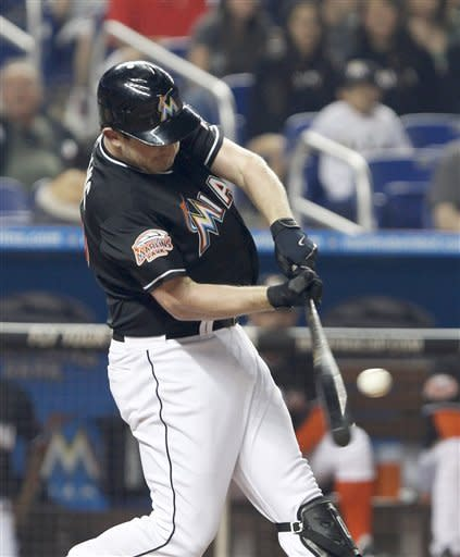 Miami Marlins' Austin Kearns hits a home run, scoring Omar Infante, during the first inning of a baseball game against the New York Mets, Friday, May 11, 2012, in Miami. (AP Photo/Wilfredo Lee)