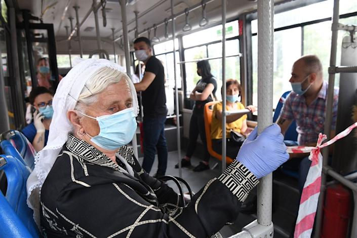 Passengers wear protective face masks as they ride a bus in Tirana, Albania, on July 6, 2020.