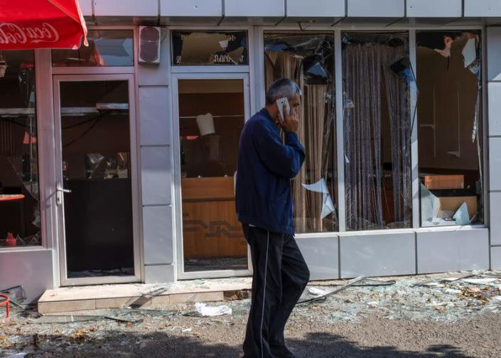 A man walks past a building that was allegedly damaged by recent shelling during a military conflict over the breakaway region of Nagorno-Karabakh