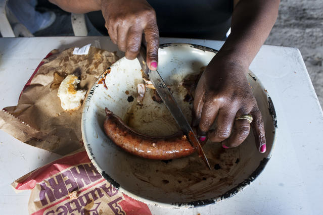 <p>A woman has breakfast with a sausage, cooked in a street braai (a typical South African BBQ), in the township of Khayelitsha, one of the poorest areas of Cape Town. (Photograph by Silvia Landi) </p>