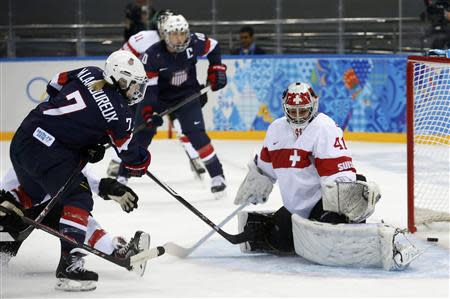 Team USA's Monique Lamoureux (L) scores on Switzerland's goalie Florence Schelling during the first period of their women's preliminary round hockey game at the Sochi 2014 Winter Olympic Games February 10, 2014. REUTERS/Mark Blinch