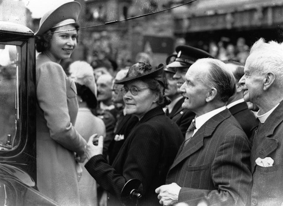 <p>The day after V-E Day, Princess Elizabeth, who worked as a mechanic during the war, greets crowds as she tours London's West End. </p>