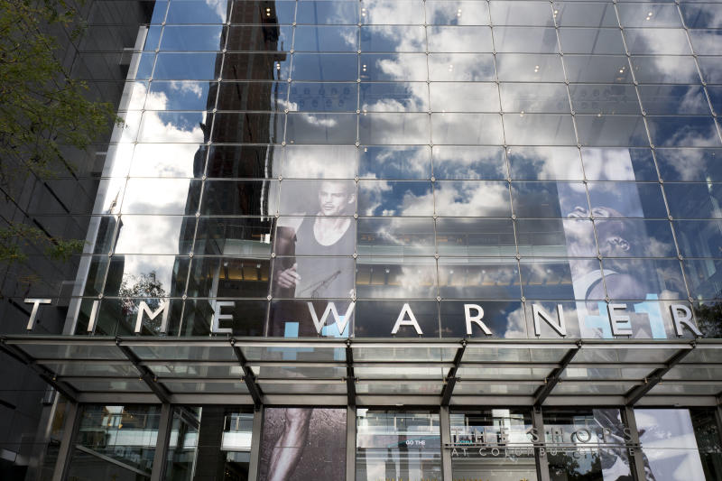 FILE - In this Oct. 24, 2016, file photo, clouds are reflected in the glass facade of the Time Warner building in New York. The Justice Department intends to sue AT&T to stop its $85 billion purchase of Time Warner, according to a person familiar with the matter who was not authorized to discuss the suit ahead of its official filing. (AP Photo/Mark Lennihan, File)