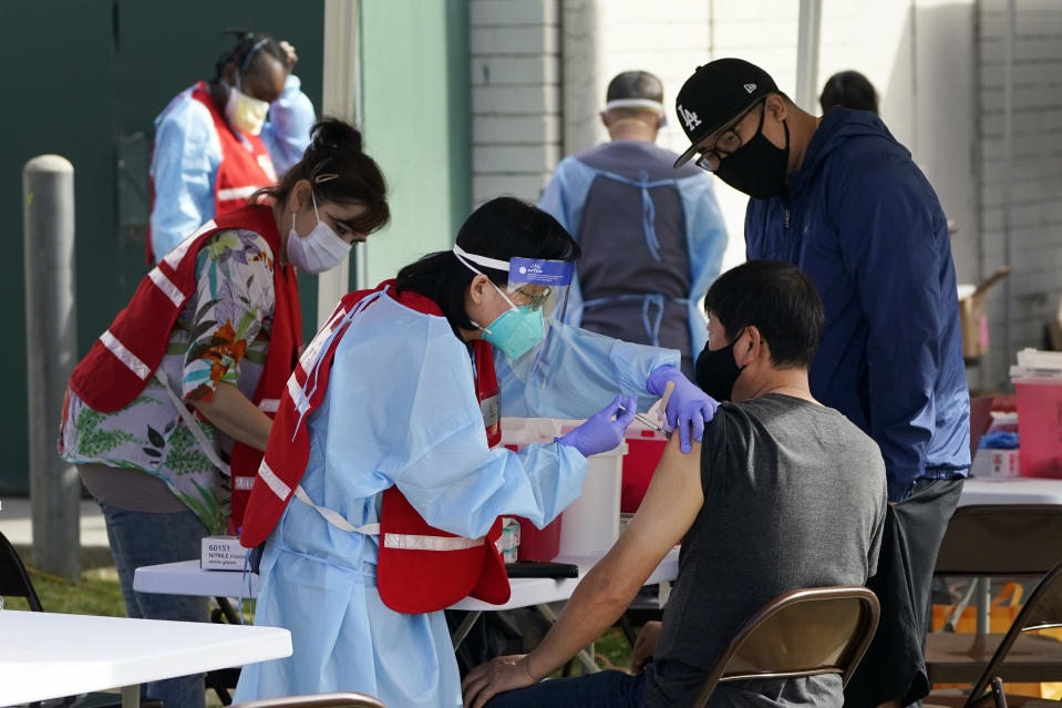 Health care workers receive a COVID-19 vaccination at Ritchie Valens Recreation Center, Wednesday, Jan. 13, 2021, in Pacoima, Calif. (AP Photo/Marcio Jose Sanchez)
