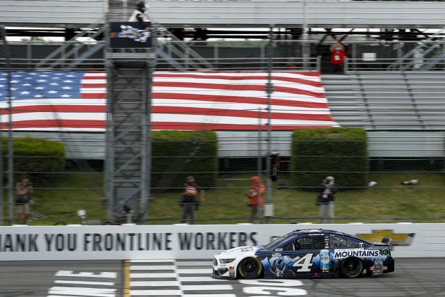 Kevin Harvick takes the checkered flag as he crosses the finish line to win a NASCAR Cup Series auto race at Pocono Raceway, Saturday, June 27, 2020, in Long Pond, Pa. (AP Photo/Matt Slocum)