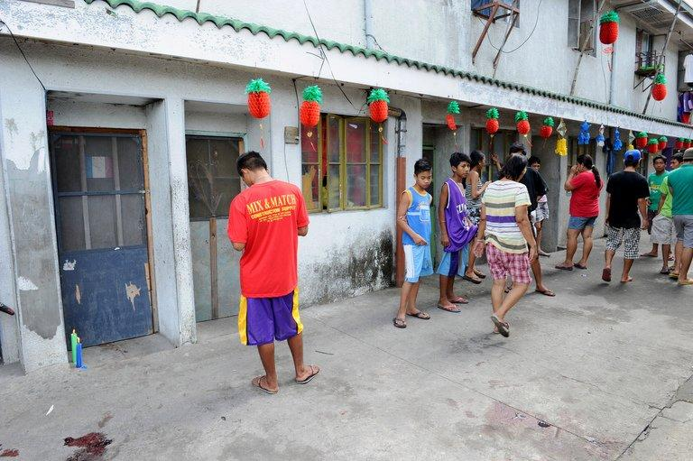 Residents walk past a door with candles (L) and blood stains after a shooting rampage in Kawit, on January 4, 2013