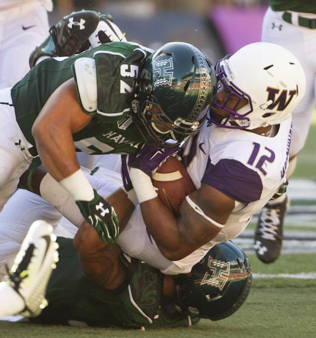 Hawaii linebacker Tevita Lataimua (52) and linebacker TJ Taimatuia, bottom, tackle Washington running back Dwayne Washington (12) in the first quarter of an NCAA college football game, Saturday, Aug. 30, 2014, in Honolulu. (AP Photo/Eugene Tanner)