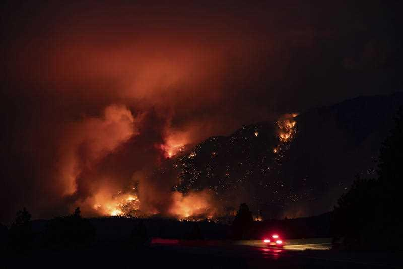 A motorist travels on the Trans-Canada Highway as a wildfire burns on the side of a mountain in Lytton.