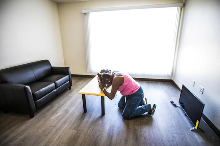 A woman prays inside a sparsely furnished apartment