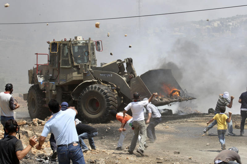 Palestinians throw rocks at an Israeli army bulldozer during clashes in the northern West Bank village of Kufr Qaddum, near the Jewish settlement of Kdumim, Friday, May 18, 2012. (AP Photo/Nasser Ishtayeh)