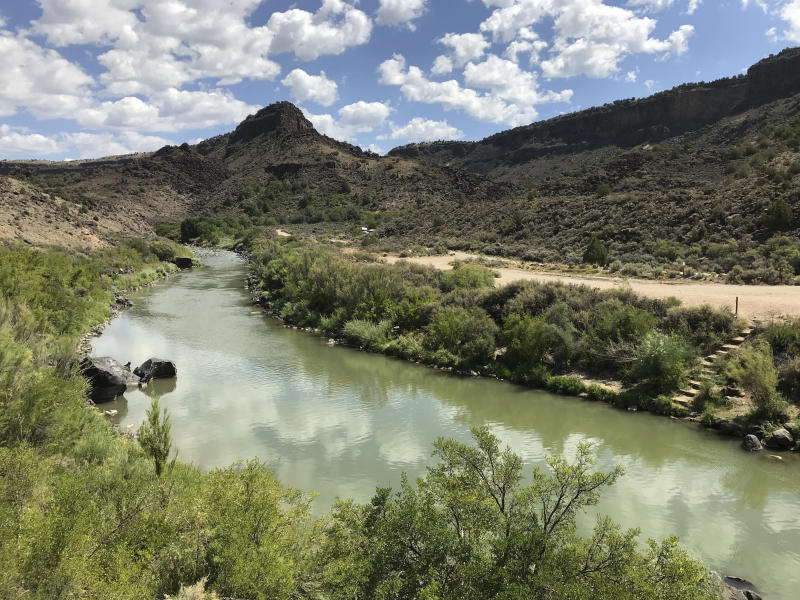 This Aug. 6, 2018, photo shows the Rio Grande flowing south of Taos, New Mexico. A recent report by the U.S. Geological Survey found that investments made to reduce the risk of wildfire and to protect water sources in the West are paying dividends by creating jobs and infusing money into local economies. The study focused on several counties along the New Mexico-Colorado border that make up the watershed of the Rio Grande, one of North America's longest rivers. (AP Photo/Susan Montoya Bryan)