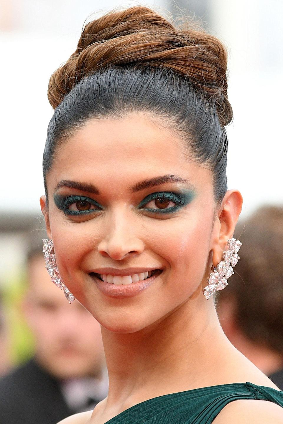 """<p>Padukone took <a rel=""""nofollow noopener"""" href=""""http://www.harpersbazaar.co.uk/fashion/style-files/news/g36775/one-tone-dressing/"""" target=""""_blank"""" data-ylk=""""slk:one-tone dressing"""" class=""""link rapid-noclick-resp"""">one-tone dressing</a> to the Cannes red carpet <a rel=""""nofollow noopener"""" href=""""http://www.harpersbazaar.co.uk/awards-season/news/g37516/threes-a-trend-matching-eye-makeup-dress-red-carpet-golden-globes/"""" target=""""_blank"""" data-ylk=""""slk:co-ordinating her eyeshadow"""" class=""""link rapid-noclick-resp"""">co-ordinating her eyeshadow</a>, dress and shoes to the same deep forest green shade. </p>"""