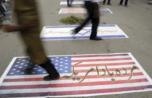Pakistani demonstrators walk over US and Israeli flags in Islamabad,during a demonstration against the anti-Islam film