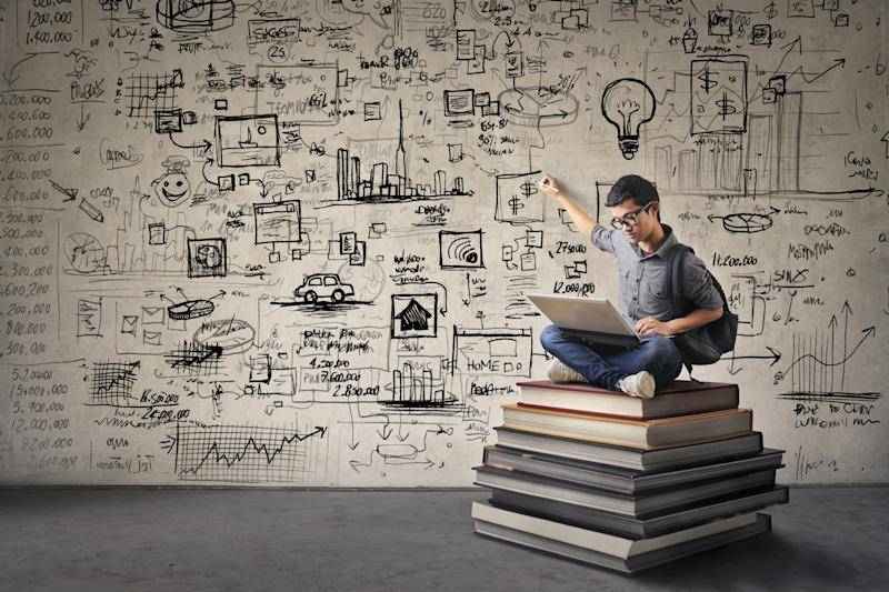 A man sitting on a stack of books while pointing at diagrams written on the wall behind him.
