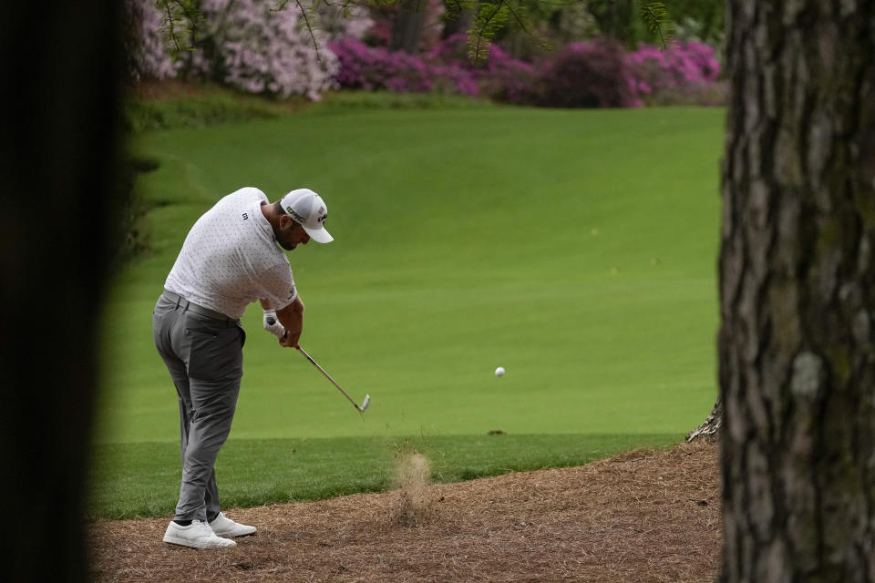 Jon Rahm, of Spain, hits out of the pine straw on the 13th hole during the second round of the Masters golf tournament on Friday, April 9, 2021, in Augusta, Ga. (AP Photo/Charlie Riedel)