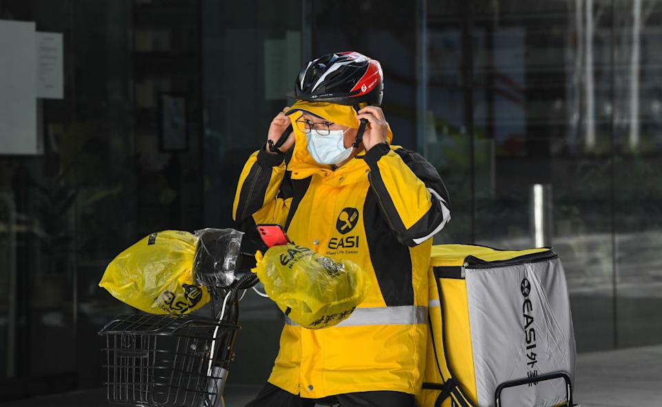 A food delivery cyclist puts on their helmet before delivery in Sydney, Australia.