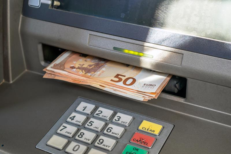 ATM and cash money. Euros withdrawal from an ATM machine, closeup view
