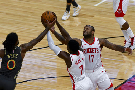 Chicago Bulls guard Coby White (0) blocks the ball against Houston Rockets guard Victor Oladipo (7) and forward P.J. Tucker (17) during the first half of an NBA basketball game Monday, Jan. 18, 2021, in Chicago. (AP Photo/Matt Marton)