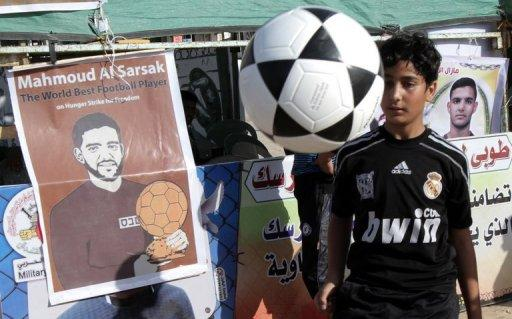 The Palestinian boy plays with a football in front of banners in solidarity with Palestinian prisoner Mahmud Al-Sarsak