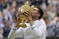 Serbia's Novak Djokovic kisses the winners trophy after he defeated Italy's Matteo Berrettini in the men's singles final on day thirteen of the Wimbledon Tennis Championships in London, Sunday, July 11, 2021. (AP Photo/Kirsty Wigglesworth)