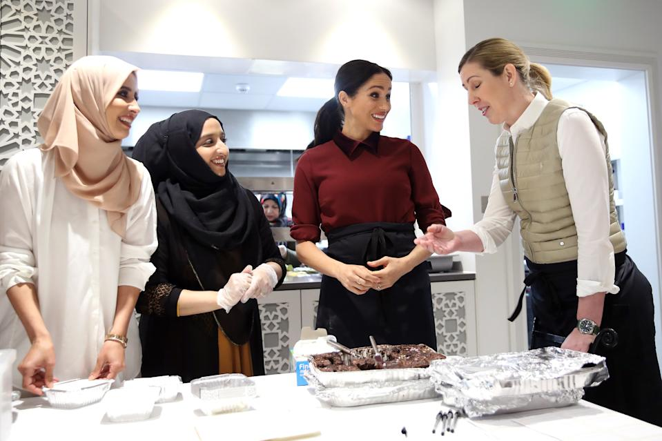 LONDON, ENGLAND - NOVEMBER 21: Meghan, Duchess of Sussex, chef Clare Smyth (R) and kitchen co-ordinator Zaheera Sufyaan (2L) as she visits the Hubb Community Kitchen to see how funds raised by the 'Together: Our Community' Cookbook are making a difference at Al Manaar, North Kensington on November 21, 2018 in London, England. (Photo by Chris Jackson/Getty Images)