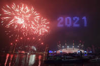Fireworks and drones illuminate the night sky over London as they form a light display as London's normal New Year's Eve fireworks display was cancelled due to the coronavirus pandemic Thursday Dec. 31, 2020. (Victoria Jones/PA via AP)