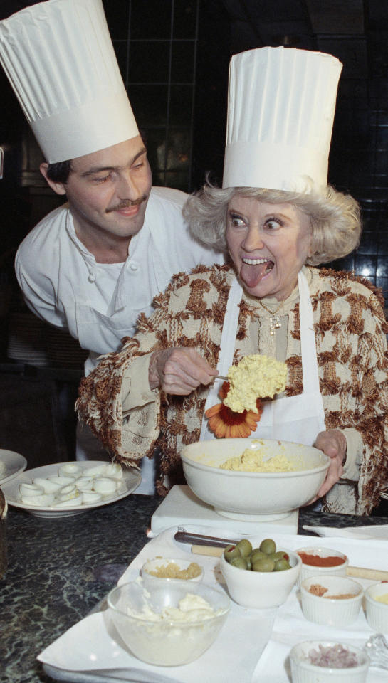 Comedian Phyllis Diller, right, reacts Friday, Nov. 9, 1990  in Boston as she mixes up a recipe for deviled eggs, as chef Douglas A. Hewson of Grill 23, & Bar looks on. (AP Photo/John Cetrino)