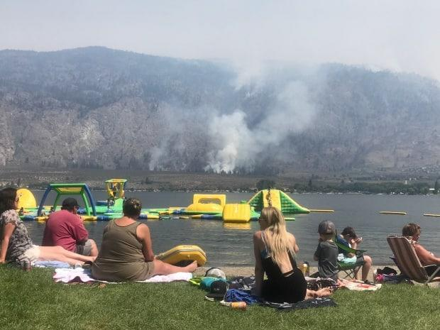 Visitors to a swim park in Osooyos look on as the Nk'Mip wildfire burns on the other side of Osooyos Lake. (Brady Strachan/CBC - image credit)