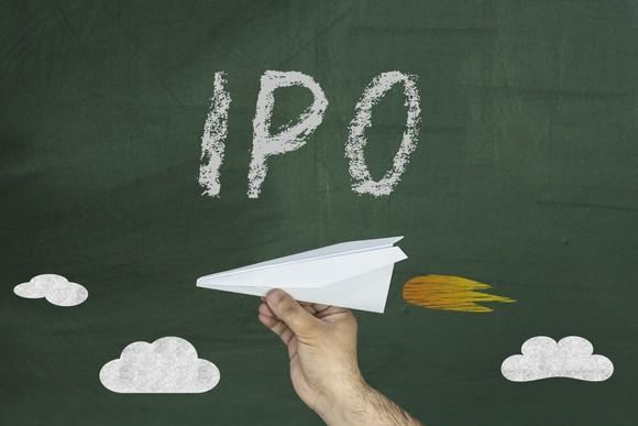 IPO written on chalkboard with hand holding paper airplane below it