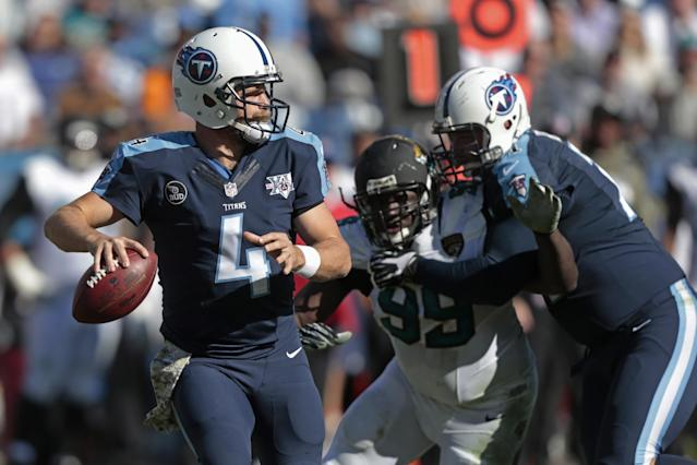 Tennessee Titans quarterback Ryan Fitzpatrick (4) passes as Titans tackle Michael Roos, right, blocks Jacksonville Jaguars defensive tackle Sen'Derrick Marks (99) in the first half of an NFL football game on Sunday, Nov. 10, 2013, in Nashville, Tenn. (AP Photo/Wade Payne)