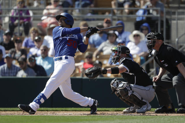FILE - In this Feb. 24, 2020, file photo, Los Angeles Dodgers' Mookie Betts, left, flies out as Chicago White Sox catcher Zack Collins, right, looks on during the first inning of a spring training baseball game in Glendale, Ariz. Fifteen games were generated Thursday, March 26, 2020, by Strat-O-Matic _ one for every game postponed on opening day because of the coronavirus. The results were produced by computer simulations, which the New York-based company will continue to run daily while the real thing is on hiatus. (AP Photo/Gregory Bull, File)
